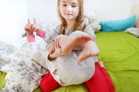 Two little sisters fooling around, playing and having fun in bed on sunny sunday morning Stock Photo