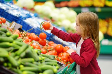 comiendo cereal: Niña elección de los tomates en una tienda de alimentos o un supermercado