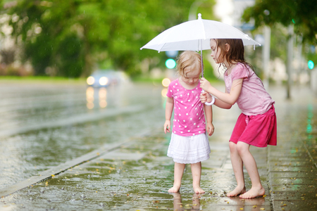 barefoot girls: Two cute little sisters standing in a puddle holding umbrella on a rainy summer day