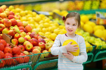 produce departments: Little girl choosing a melon in a food store or a supermarket