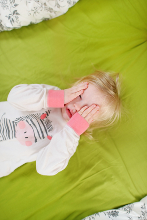 naptime: Little toddler girl playing in bed on sunny morning