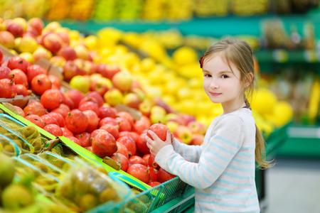 supermarket shopper: Little girl choosing pomegranates in a food store or a supermarket
