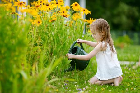 Leuk meisje planten water geven in de tuin Stockfoto - 41693577