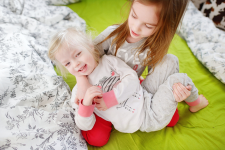 naptime: Two little sisters fooling around, playing and having fun in bed on sunny sunday morning Stock Photo