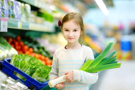 produce departments: Little girl choosing a leek in a food store or supermarket
