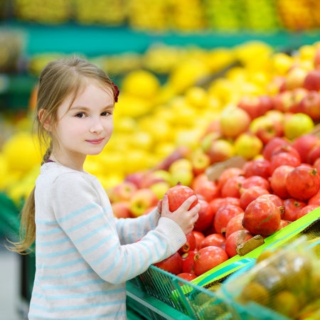 produce departments: Little girl choosing pomegranates in a food store or a supermarket