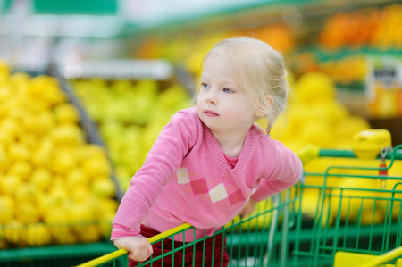 produce departments: Cute little toddler girl shopping in a food store or a supermarket Stock Photo
