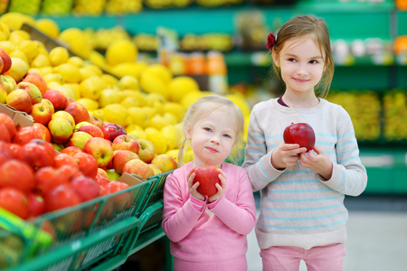 produce departments: Cute little sisters choosing apples in a food store or a supermarket