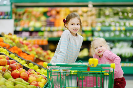 eating fruit: Cute little sisters shopping in a food store or a supermarket