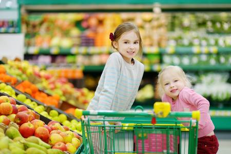 Pequeñas hermanas lindas de compras en una tienda de alimentos o de un supermercado