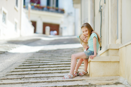 conversano: Two adorable little sisters laughing and hugging each other on warm and sunny summer day in italian town