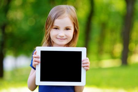 Bambina felice che tiene tablet PC all'aperto nel parco d'estate sulla bella giornata di sole