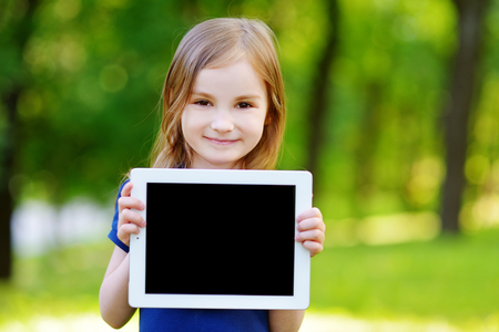 Happy little girl holding tablet PC outdoors in summer park on beautiful sunny day