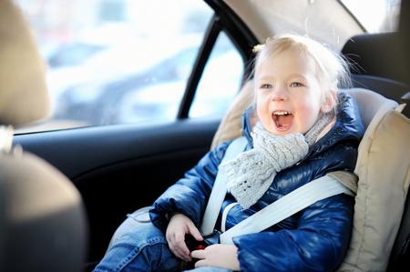 cinturón de seguridad: Niña adorable que se sienta segura en un asiento de coche