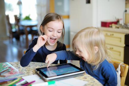 riendo: Dos pequeñas hermanas adorables que juegan con una tableta digital en el hogar