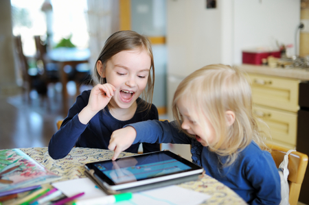 preschool: Two adorable little sisters playing with a digital tablet at home