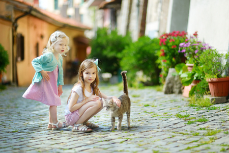 ot: Two adorable little sisters met a cat while walking narrow streets ot typical italian town