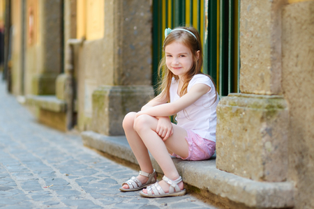 doorstep: Adorable little girl sitting on a doorstep on warm and sunny summer day in typical italian town Stock Photo