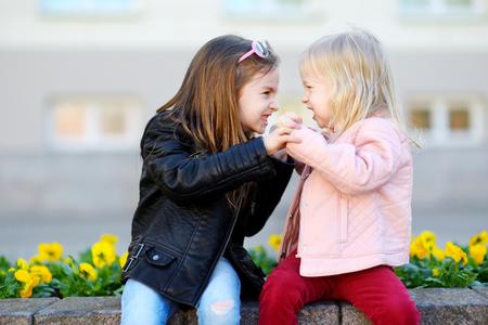 야외에서 싸우는 두 어린 자매