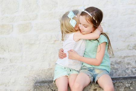 Two adorable little sisters laughing and hugging each other on warm and sunny summer day in italian town