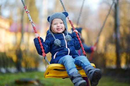 freddo: Ragazza adorabile divertirsi su un'altalena sulla bella giornata autunnale Archivio Fotografico