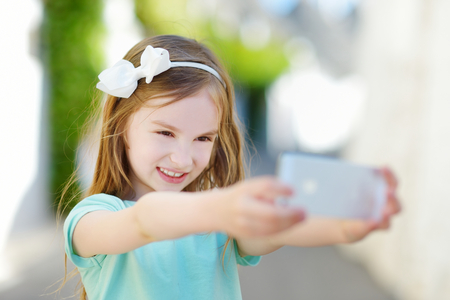 fancy girl: Adorable little girl taking a photo of herself with a smartphone on beautiful summer day Stock Photo