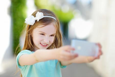 jolie petite fille: Adorable petite fille de prendre une photo d'elle-même avec un smartphone sur la belle journée d'été Banque d'images