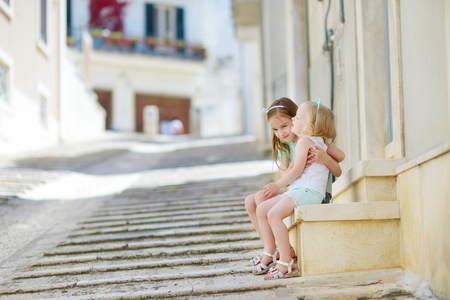 conversano: Two adorable little sisters laughing and hugging on warm and sunny summer day in italian town