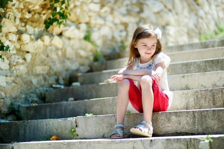 familias jovenes: Niña adorable que se sienta en las escaleras en día cálido y soleado de verano en la ciudad italiana típica