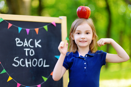 schoolgirl uniform: Adorable little schoolgirl feeling extremely excited about going back to school