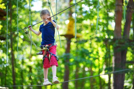 niño trepando: Adorable niña disfrutando de su tiempo en la escalada parque de aventura en día cálido y soleado de verano