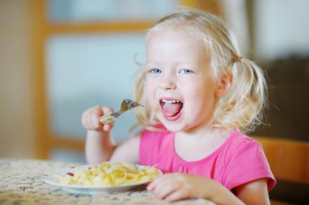 niños comiendo: Lindos divertidos niña comiendo espagueti