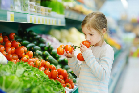 produce departments: Little girl choosing tomatoes in a food store or a supermarket