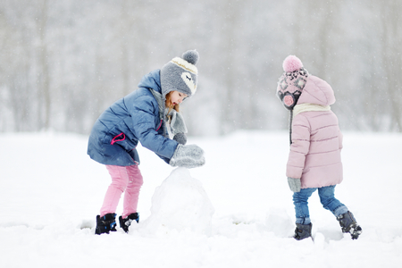 together: Two funny adorable little sisters making a snowman together in beautiful winter park during snowfall