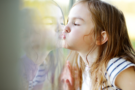 Cute funny little girl kissing her reflection on a window glass Standard-Bild