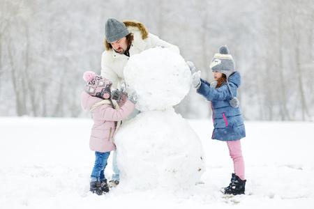 bonhomme de neige: Un jeune père et ses deux filles construire un bonhomme de neige le jour de l'hiver Banque d'images