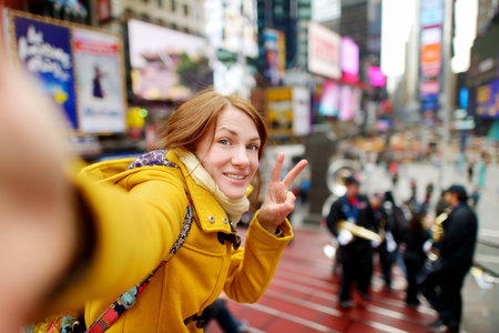 winter time: Beautiful young woman taking a selfie with her smartphone on Times Square, New York Stock Photo