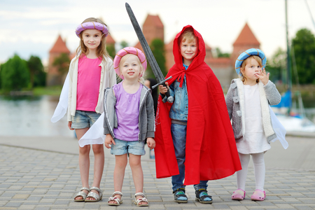 Four kids in princesses and a knight costumes having fun outdoors Stok Fotoğraf