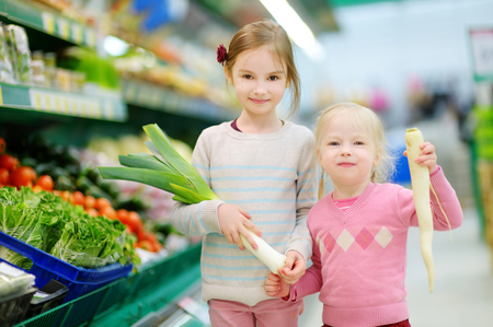 eating fruits: Cute little sisters shopping in a food store or a supermarket