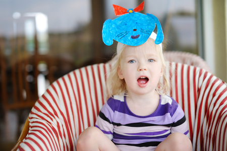 phantasy: Cute little toddler girl with a self made puppy dog mask Stock Photo