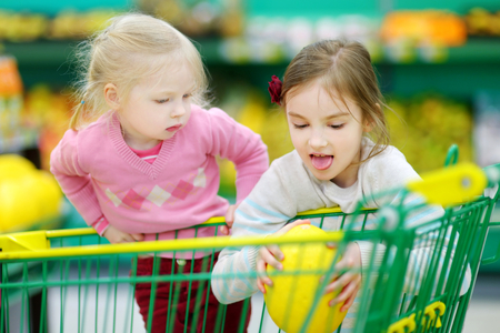 produce departments: Cute little sisters shopping in a food store or a supermarket
