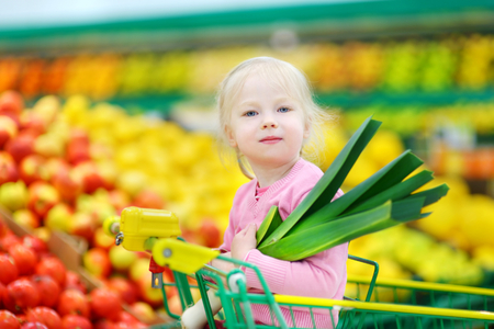 produce departments: Cute little girl sitting in a shopping cart holding a leek in a food store