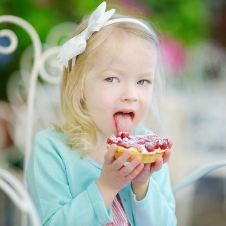 niños comiendo: Niña adorable que come fresca torta dulce fresa al aire libre en día cálido y soleado de verano en Italia Foto de archivo