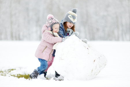 snowman: Two funny adorable little sisters making a snowman together in beautiful winter park during snowfall