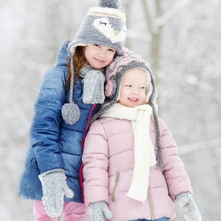 Two funny adorable little sisters having fun together in beautiful winter park during snowfall