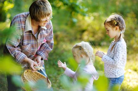 niño abrigado: Abuela y sus dos pequeños nietos recogiendo setas en el bosque Foto de archivo