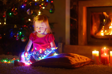 christmas tree: Adorable little girl playing with Christmas lights by a fireplace in dark and cozy dining room Stock Photo