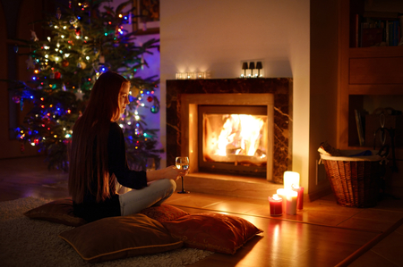 fire house: Woman having a drink by a fireplace in a cozy dark living room on Christmas eve