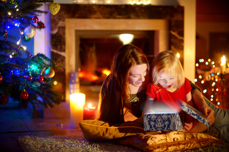 young people fun: Young mother and her little daughter opening a magical Christmas gift by a Christmas tree in cozy living room in winter Stock Photo