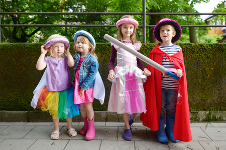Four kids dressed in princesses and a knight costumes having fun outdoors